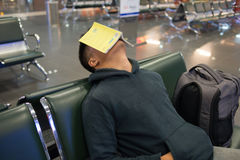 Man sleeping in the airport with book on face. Young man sleeping in the airport with book on his face royalty free stock photo