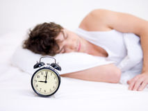 Man sleeping with alarm clock Royalty Free Stock Images