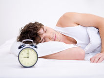 Man sleeping with alarm clock Stock Image