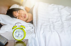 Man sleeping with alarm clock in foreground. Man sleeping on bed with alarm clock in foreground Royalty Free Stock Photos
