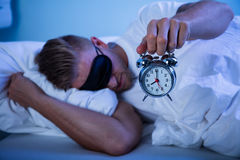 Man Sleeping With A Alarm Clock In His Hand. Man Sleeping On Bed By Holding Alarm Clock In His Hand Stock Photography