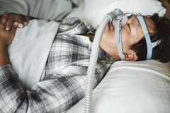 A man sleeping with anti snoring chin strap Stock Photography
