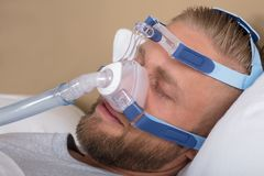 Man With Sleeping Apnea And CPAP Machine. Young Man Lying On Bed With Sleeping Apnea And CPAP Machine royalty free stock photos