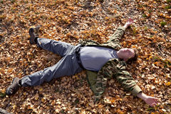 Man sleeping on the autumn field. Man sleeping on the field with yellow leaves Stock Image