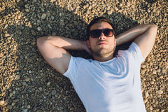 Man sleeping on the beach. Man wearing sunglasses sleeping on the beach Royalty Free Stock Image