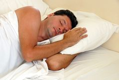 Man sleeping in bed. Mature man sleeping on white pillow in bed Royalty Free Stock Images