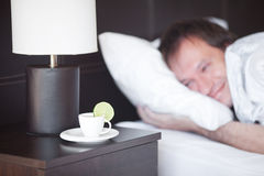 Man sleeping on a bed. A cup of tea on the bedside table and lamp Royalty Free Stock Image