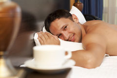 Man sleeping on a bed. A cup of tea on the bedside table and lamp Stock Photo