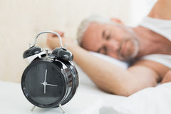 Man sleeping in bed with alarm clock in foreground. Mature man sleeping in bed with alarm clock in foreground at bedroom Royalty Free Stock Photography