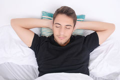 Man sleeping on bed. Close-up of attractive young man sleeping on her bed. Indoors Stock Photography