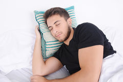 Man sleeping on bed. Close-up of attractive young man sleeping on her bed. Indoors Stock Photos