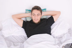 Man sleeping on bed. Close-up of attractive young man sleeping on her bed. Indoors Stock Image