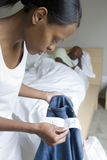 Man sleeping in bed, focus on woman holding pair of jeans and receipt in foreground, side view Stock Image