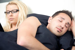 Man sleeping in bed with his wife Royalty Free Stock Photo