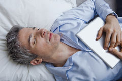 Man sleeping on bed with holding a digital tablet Stock Photography