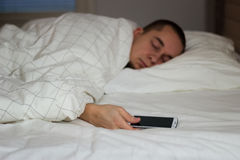 Man sleeping in bed and holding a mobile phone Stock Photos