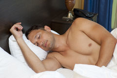 Man sleeping on the bed at home Stock Photography
