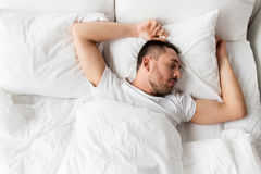 Man sleeping in bed at home. People, bedtime and rest concept - man sleeping in bed at home Royalty Free Stock Photo