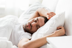 Man sleeping in bed at home. People, bedtime and rest concept - man sleeping in bed at home Royalty Free Stock Photography