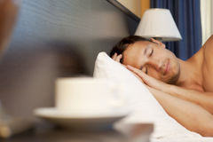 Man sleeping on a bed. morning tea. Man sleeping on a bed, a cup of tea on the bedside table and lamp Royalty Free Stock Image