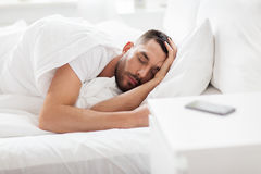 Man sleeping in bed with smartphone on nightstand. People, bedtime and rest concept - man sleeping in bed at home with smartphone on nightstand royalty free stock photos