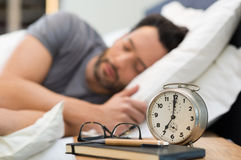 Man sleeping in bed. Young man sleeping in his bedroom. Man sleeping with an alarm clock in foreground. A calm man in his bed before waking up in his room. Close Royalty Free Stock Photography
