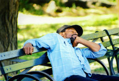 Man is sleeping on a bench in New-York. Stock Photography