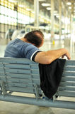 Man sleeping on a bench in the railway station Royalty Free Stock Photos