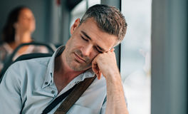 Man sleeping on the bus. Tired man sitting on the bus and sleeping, he is leaning on his arm Royalty Free Stock Photography
