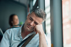Man sleeping on the bus. Tired man sitting on the bus and sleeping, he is leaning on his arm stock photography