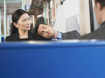 Man Sleeping on Businesswoman's Shoulder In Train Royalty Free Stock Image
