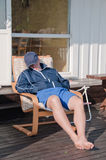 Man sleeping in a chair on a terrace. Tired man sleeping in a chair on a terrace royalty free stock photo