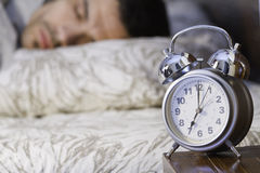 A man sleeping close to a retro alarm clock Royalty Free Stock Photography