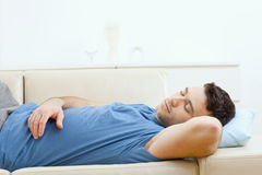 Man sleeping on couch. Young handsome man sleeping on couch at home, side view royalty free stock photo