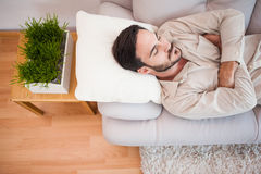 Man sleeping on the couch with arms crossed Stock Image
