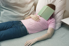Man sleeping on couch with book on his head Stock Images
