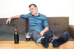Man sleeping on couch with bottle of beer on table Royalty Free Stock Photos