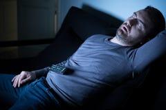 Bored man sleeping and watching tv at night Royalty Free Stock Photography