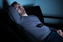 Man sleeping on the couch in front of television screen. Bored man sleeping and watching tv at night Stock Photo