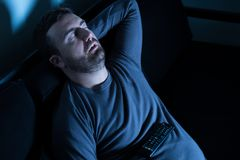 Bored man sleeping and watching tv at night. Man sleeping on the couch in front of television screen Stock Photos