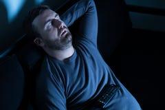 Bored man sleeping and watching tv at night Stock Photos