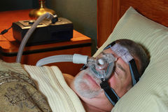 Man Sleeping with CPAP. A man is wearing a CPAP (continuous positive airway pressure) mask as he sleeps Royalty Free Stock Photography