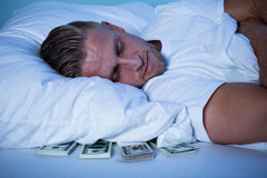 Man Sleeping With Currency Notes Kept Under His Pillow Royalty Free Stock Image