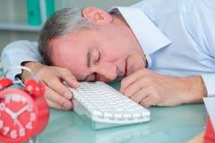 Man sleeping on desk in bright modern office. Man sleeping on his desk in bright modern office Stock Photos