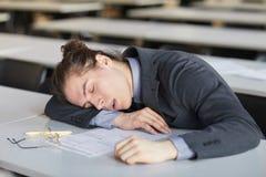 Man sleeping on desk in school