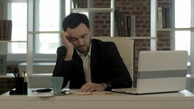 Man sleeping on a desk, wake up and start talking phone. Professional shot in 4K resolution. You can use it e.g. in your commercial video, business Stock Images