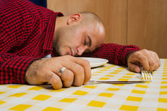 Man sleeping at the dinner table Royalty Free Stock Photos