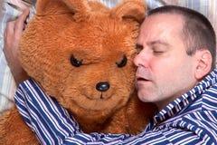 Man sleeping in an embrace with a teddy bear Stock Photo