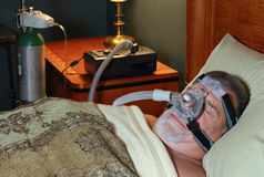 Man Sleeping (Front View) with CPAP and Oxygen. A man is wearing a CPAP (continuous positive airway pressure) mask and Oxygen as he sleeps. Selective focus on Stock Images