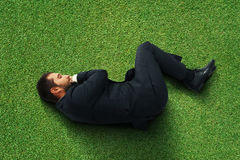 Man sleeping on the green grass Stock Images